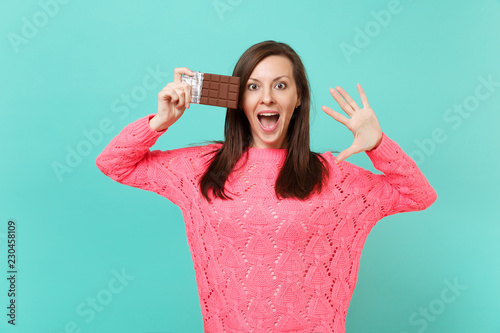 Excited young woman in knitted pink sweater hold in hand chocolate bar, showing palm keeping mouth wide open isolated on blue background, studio portrait Fototapet