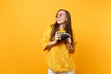 Laughing Pretty Young Woman In Fur Sweater And Heart Eyeglasses Holding Retro Vintage Photo Camera Isolated On Bright Yellow Background. People Sincere Emotions Lifestyle Concept. Advertising Area.