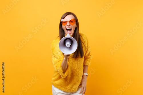 Photographie Portrait of crazy young woman in fur sweater and orange heart eyeglasses screaming on megaphone isolated on bright yellow background