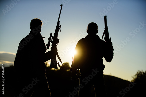 Foto op Canvas Jacht Hunting with partner provide greater measure safety fun and rewarding. Hunters friends gamekeepers with guns silhouette sky background. Hunters rifles nature environment. Hunter friend enjoy leisure