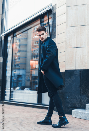 Portrait of young handsome stylish man in elegant coat