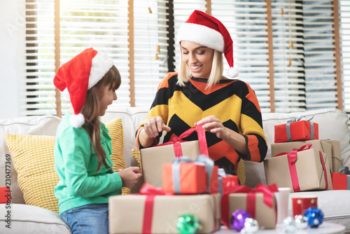Photo  Young mother and her daughter are unwrapping gift or present boxes