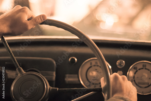 Poster Vintage voitures driving a vintage car; only the driver's hand on the steering wheel are visible, the dashboard is blurred; stylized as an old sepia photo with dust and noise