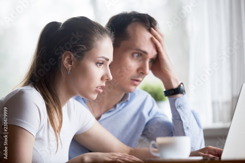 Cuadros en Lienzo Head shot young millennial anxious spouses looking at computer screen