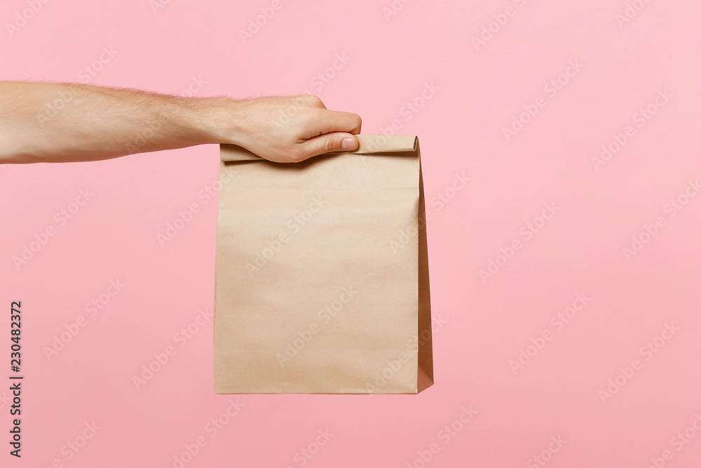 Fototapeta Close up male holding in hand brown clear empty blank craft paper bag for takeaway isolated on pastel pink background. Packaging template mock up. Delivery service concept. Copy space advertising area