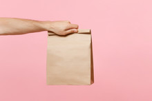 Close Up Male Holding In Hand Brown Clear Empty Blank Craft Paper Bag For Takeaway Isolated On Pastel Pink Background. Packaging Template Mock Up. Delivery Service Concept. Copy Space Advertising Area