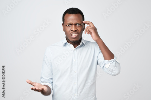 Young european man in white shirt dissatisfied frowns and looks sullenly Wallpaper Mural