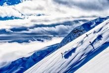 Skiers Skiing Down A Steep Mountain