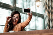 canvas print picture Playful mood. Delighted brunette woman looking at her gadget while taking picture