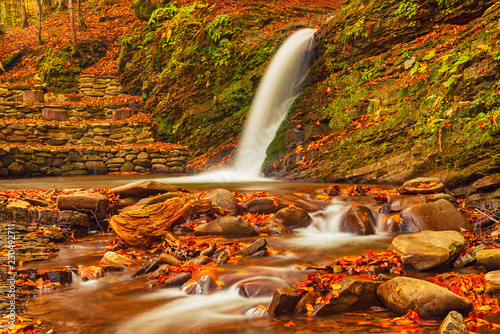 Fotografiet  Autumn mountain waterfall stream in the rocks with colorful red fallen dry leave