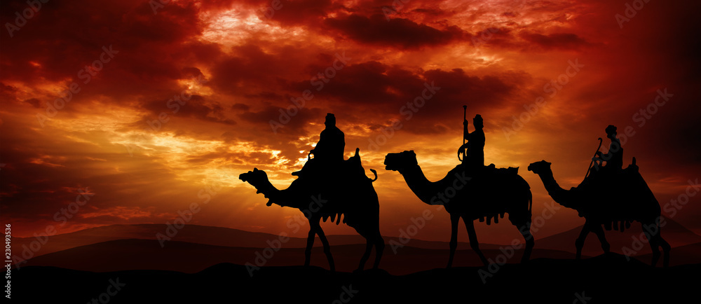 Fototapeta Three kings - traveling in the desert against the background of red clouds rising from the sun