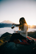 Woman Pouring A Drink While Sitting On Top Of A Rock
