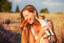 Young Woman Holding Jack Russell Terrier Puppy On Her Hand, Trying To Pose, But The Dog Is Licking And Chewing Her Ear And Hair.