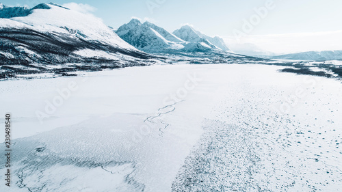 A frozen body of water with snow capped mountains in the background