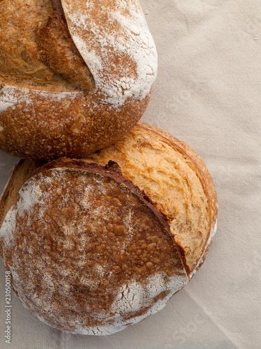 In de dag Brood Dos hogazas de pan artesano sobre un mantel de lino vistos cenitalmente