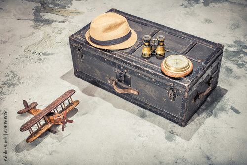Fotografie, Obraz  Vintage old classic travel trunk luggage with leather handles circa early 1900s, wooden toy plane, compass, binoculars, men's hat