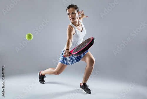 Adult fitness woman playing padel indoor. Isolated on white.