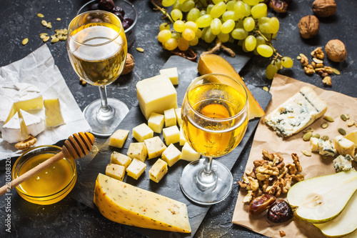 Different types of cheese on board, olive, fruits, almond and wine glasses on stone table