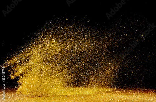 Golden powder scattered over the dark background