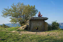 Girl Sitting And Meditating On Ancient Dolmen And Blue Sky Background