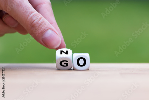 Obraz na plátně Hand is turning dice and changes the word go to no
