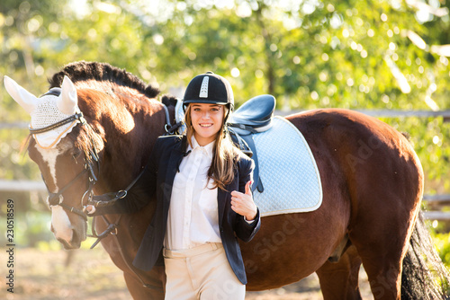 Poster Equitation Girl equestrian rider stands near the horse. Horse farm