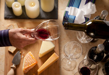 Man's Hand Holding Glass Of Wine Over Board Of Cheeses