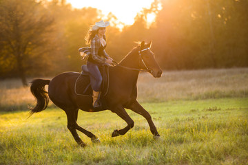 Fototapeta Girl equestrian rider riding a beautiful horse