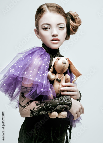 Valokuva  Beautiful girl child model in fashionable clothes holding a rabbit toy