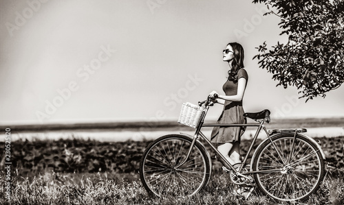 Fototapety, obrazy: girl with bicycle on country road. Image in black and white color style