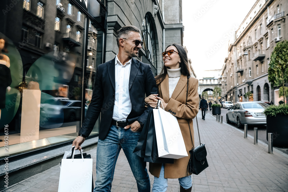 Fototapeta Shopping. Black Friday. Couple. Love. Man and woman with shopping bags are smiling while walking down the street