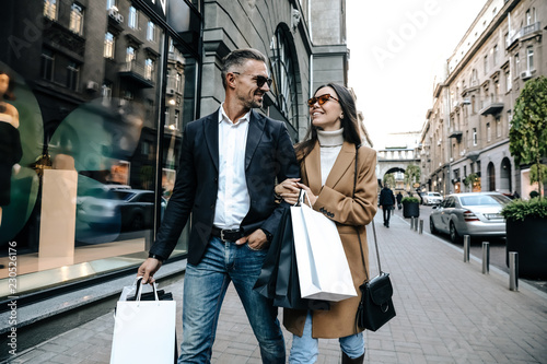Fototapeta Shopping. Black Friday. Couple. Love. Man and woman with shopping bags are smiling while walking down the street obraz