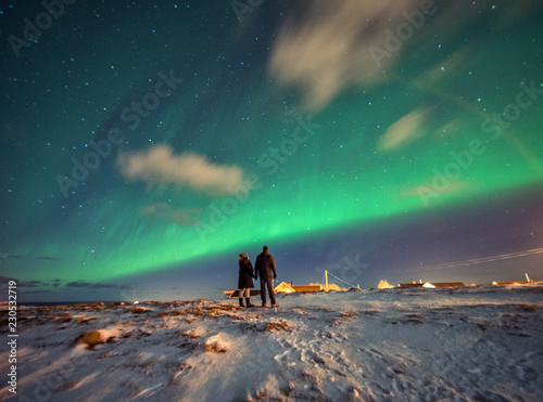 A couple admires the Northern Lights in the mountains of Reine, Norway. Lofoten Islands