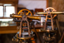Two Antique Surveyors Sextants On Wooden Tripods In Workroom Environment