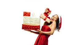 Portrait Of An Excited Woman In Santa Claus Hat Carrying Many Presents, Some Falling Down, Isolated On White Studio Background