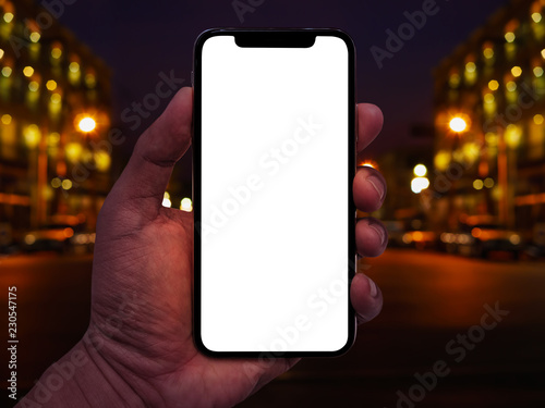 Obraz na plátně Hand holding smartphone with abstract bokeh of city night light background