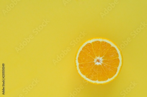 Photo Stands Slices of fruit Slice Orange fruit isolated on yellow color background for summer time with space for text.