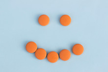 Funny Faces Of Orange Pills On A Blue Background. Concept Of Antidepressants