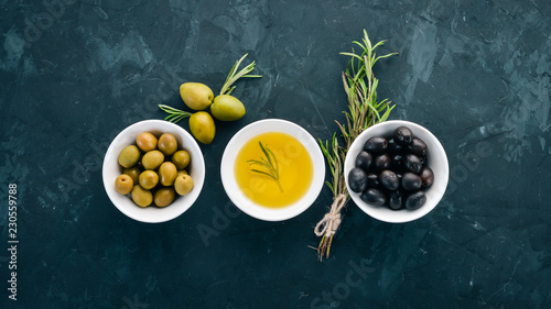 A set of olives and olive oil and rosemary. Green olives and black olives. On a black stone background. Free space for text.