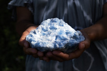 Close Up Of A Woman Holding A Powerful Healing Blue Calcite Crystal In Her Hands In Dark, Moody Light.