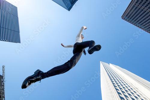 ビル街を青空バックにジャンプするYシャツ姿のビジネスマン1人。挑戦,努力,成功,元気イメージ Fototapeta