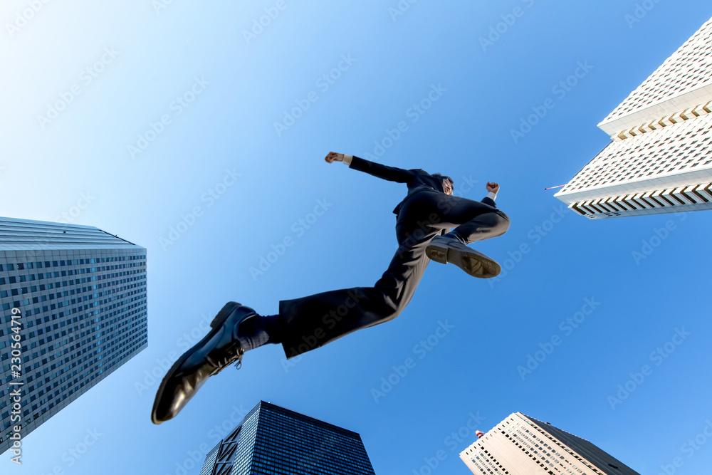 Fototapeta ビル街を青空バックにジャンプするスーツ姿のビジネスマン1人。挑戦,努力,成功,元気イメージ