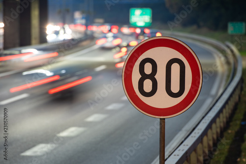 Cuadros en Lienzo  Long exposure shot of traffic sign showing 80 km/h speed limit on a highway full