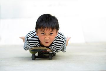 Fototapeta Funny asian boy lying on a skateboard looking to camera