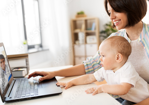 Fototapeta medicine, technology and healthcare concept - happy mother with baby son having video chat with family doctor on laptop computer at home obraz