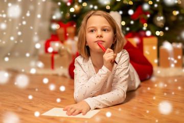 Fototapeta christmas, holidays and childhood concept - girl writing wish list or letter to santa at home