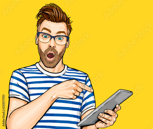 Amazed man in glasses with open mouth showing something on tablet Canvas Print