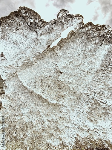 Structured frozen mud. Shore of frozen puddle against the light