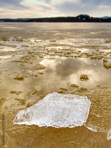 Winter natural wonder. Yellow pieces of snow melting on beach. Wonderful nature c