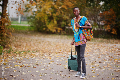 Photo African man in africa traditional shirt on autumn park with backpack and suitcase